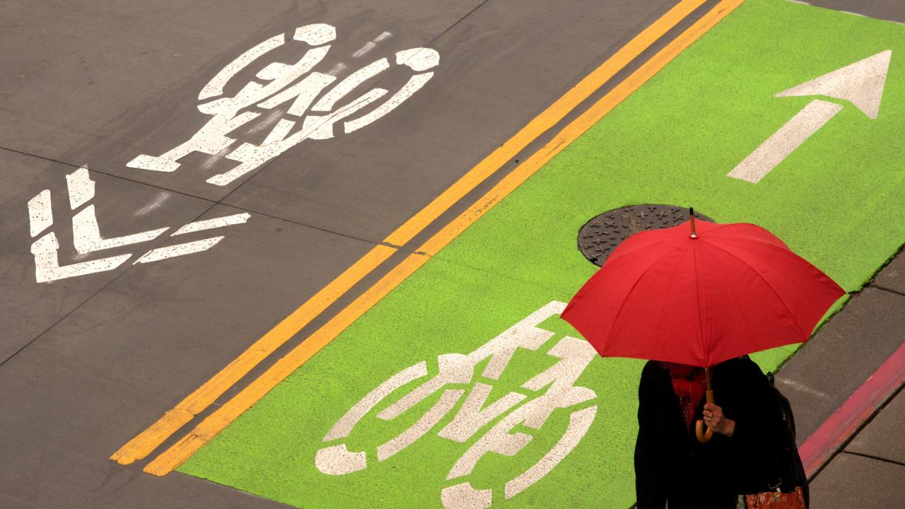 A woman with a red umbrella walks past a green bike path sign at the Transportation Bus Hu
